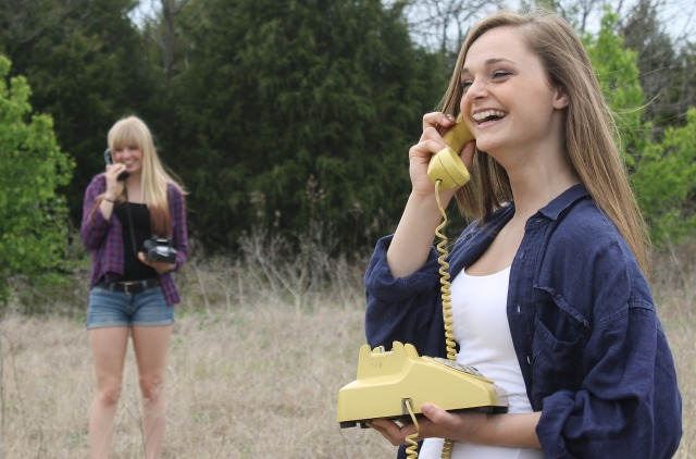 Two teenage girls standing in a field, each using a rotary telephone