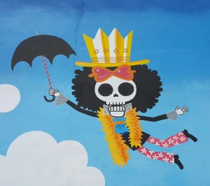 a skeleton wearing 70's clothes and a striped hat and holding an umbrella
